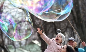 A girl reacts as she looks at soap bubbles made by a street