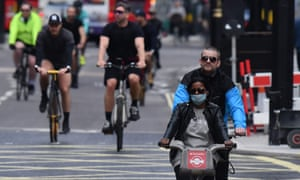 People cycling wearing face masks as a precaution are seen on Oxford Street in London