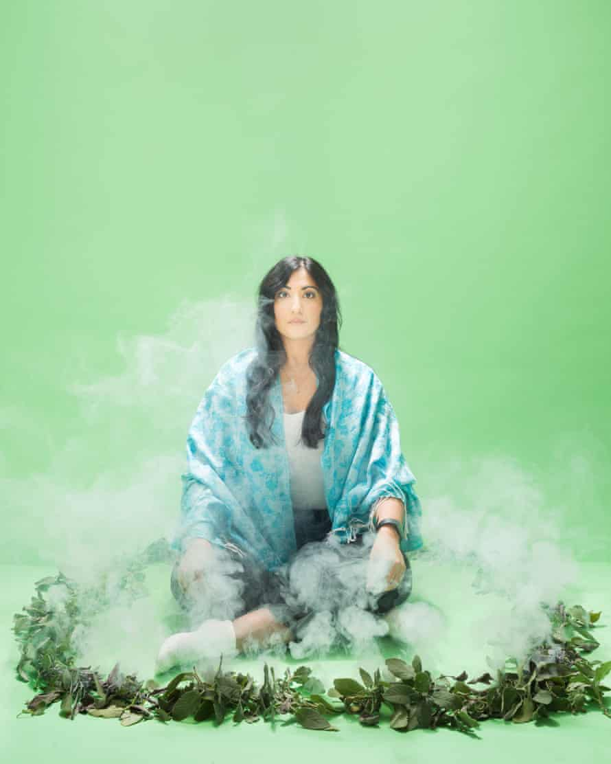 Guardian writer Coco Khan sitting in a circle of smoking leaves, against a green background
