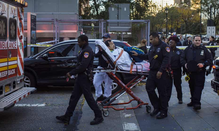 Emergency personnel carry a man into an ambulance after a truck drove onto a busy bicycle path near the World Trade Center memorial in New York.