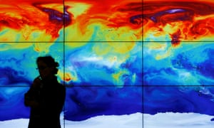 A participant is pictured in front of a screen projecting a world map during the World Climate Change Conference 2015