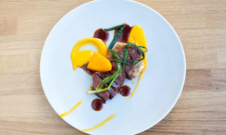 Slices of beef bavette with curls of pumpkin on a round white plate