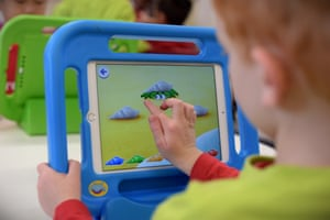 A boy plays on an iPad at an early-learning centre.