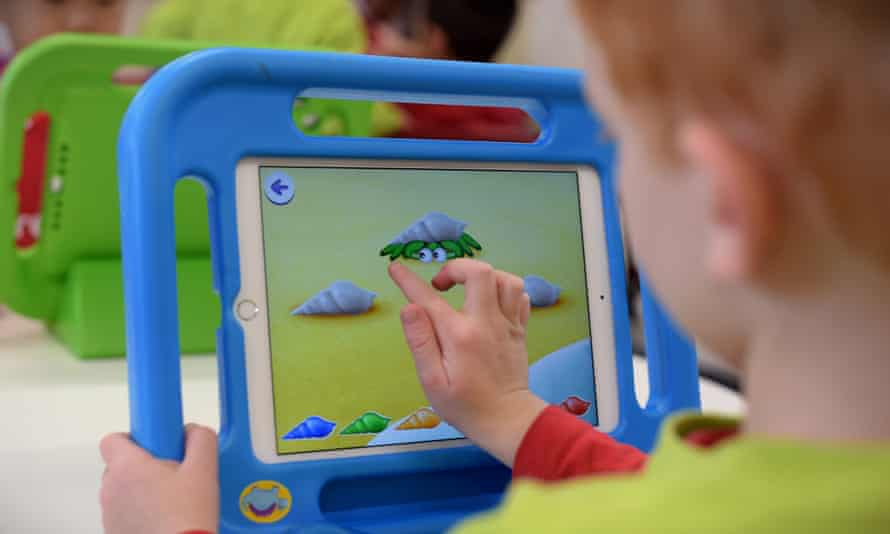 A boy plays on an iPad at an early learning school in Canberra