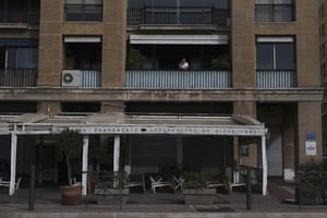 A man stands at his balcony over a closed restaurant in Marseille