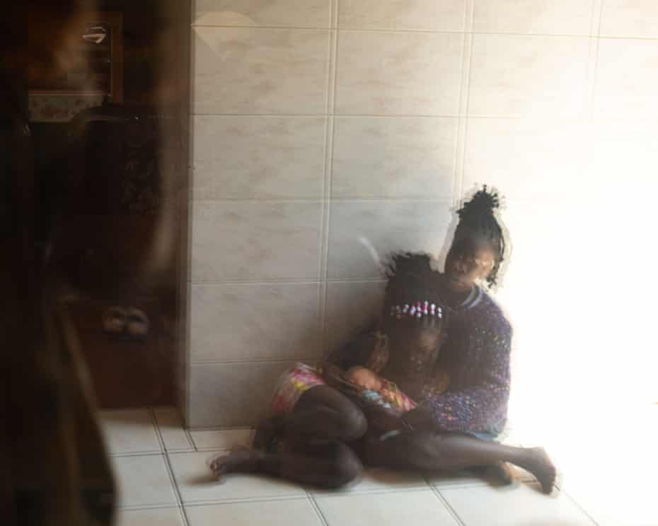 Blurry picture of Blessing holding Immy both sitting on a tiled floor.