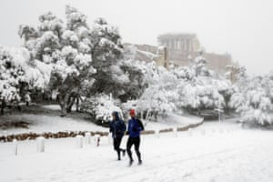 Joggers are seen in front of the Parthenon.
