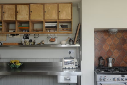 A freestanding oven with spanish tile splashback, some steel shelves and old school locker cupboards.