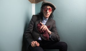 John Cooper Clarke, wearing glasses and a tweed flat cap, sitting in a corner, resting his elbow on his knee