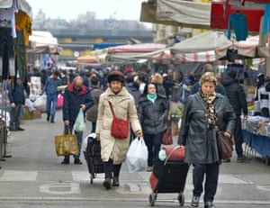 Pedestrians walk through a local market in the Corvetto district of Milan on Tuesday.