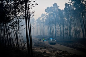 A policeman stands by the body of a victim of a wildfire in Pedrogao