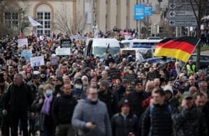 Protestors take part in a march on 20 March demanding an end to the coronavirus restrictions in Kassel, central Germany.