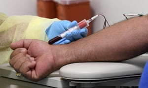 A phlebotomist takes a blood sample from a patient's arm