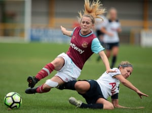 A Spurs player tackles a West Ham player in a women's football match