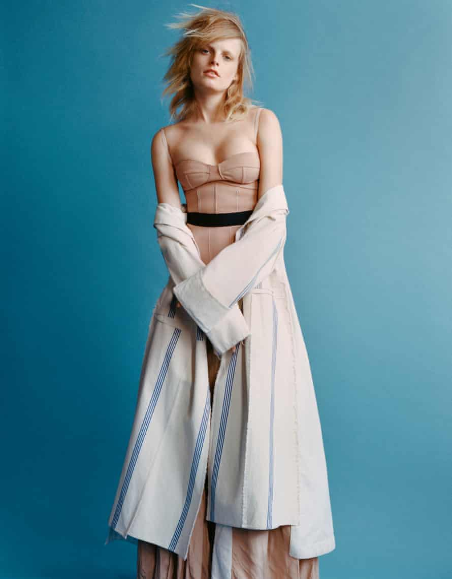 Hanne Gaby Odiele in a corset top and skirt with a coat hanging form her elbows