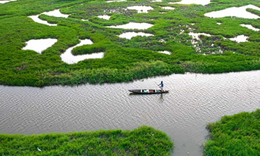 A fisher in a canoe in a wetland area of Ghana.