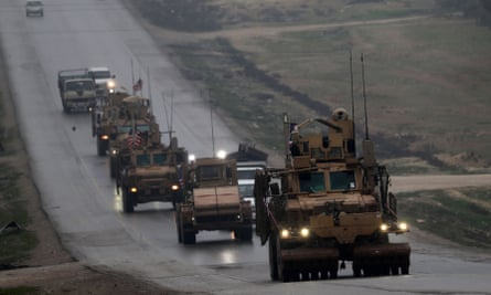 A convoy of US military vehicles travels through the northern city of Manbij in December 2018.