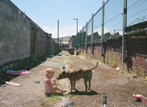 Mark's daughter Pennie with Sonny the dog, in the back alley behind their home in Darwen, Lancashire (2018)