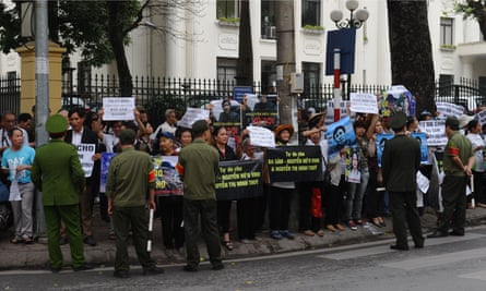Supporters hold posters including those that read 'Freedom for Basam Nguyen Huu Vinh' and 'Nguyen Huu Vinh is innocent' during a protest held in front of the People's Court in Hanoi.