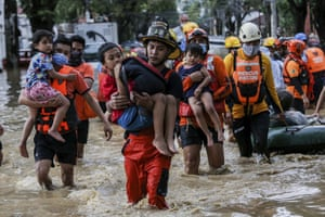 Rescuers carry children from a flooded street in Providence village in Marikina city, east of Manila