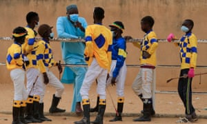 Adama Bao, a coach who owns the Lambafar stable, speaks to Diop and the other jockeys before a race at the Hippodrome