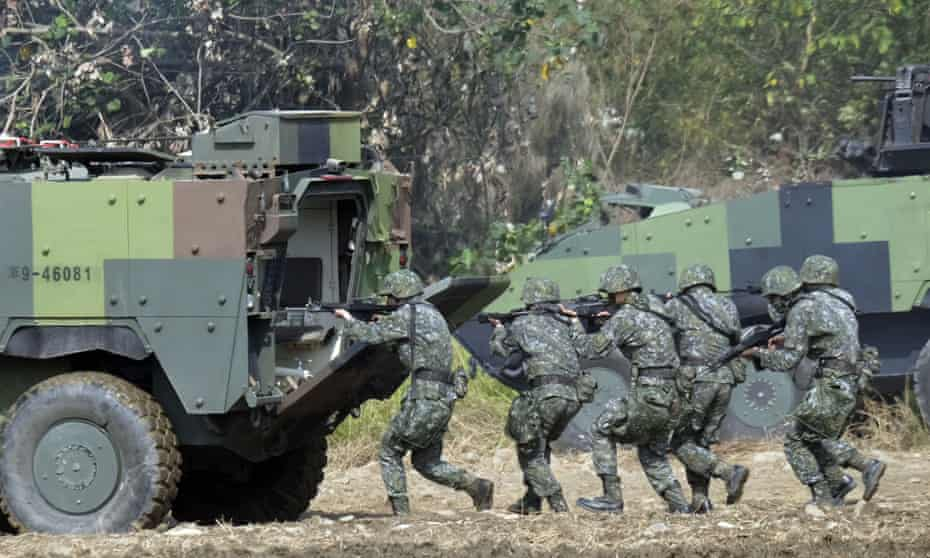 Taiwan soldiers walk behind an armoured personnel carrier during an annual military drill in Taichung, central Taiwan, in 2017.