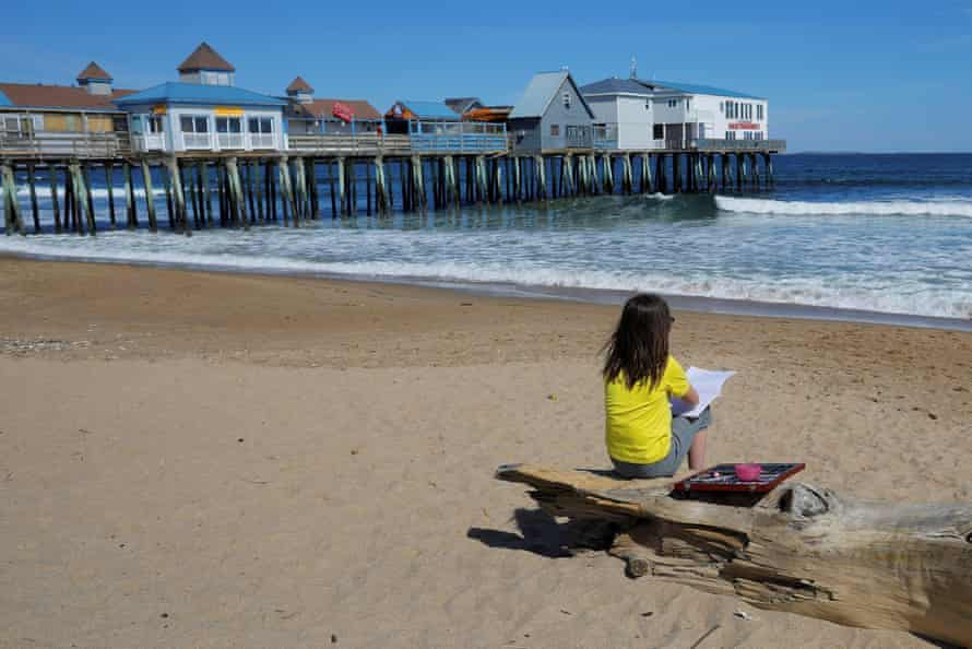A girl sketches on a deserted beach in Old Orchard Beach.