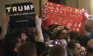 Police attempt to remove protesters as Republican presidential candidate Donald Trump speaks during a campaign rally.