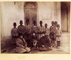 This photo was probably taken by Masoud Mirza Zell-e-Soltan (1850-1918), governor of Isfahan (1872-1907), and the eldest son of Nasser al-Din Shah. Zell-e-Soltan's son Bahram Mirza sits in the middle on a chair accompanied by two members of his court (Reza Qoli Khan, private secretary in the right and Aqabaji eunuch chief in the left) sitting on the right and eight African eunuchs. The design of the jacket and hat of the Africans slaves could be considered a type of ethnic segregation.