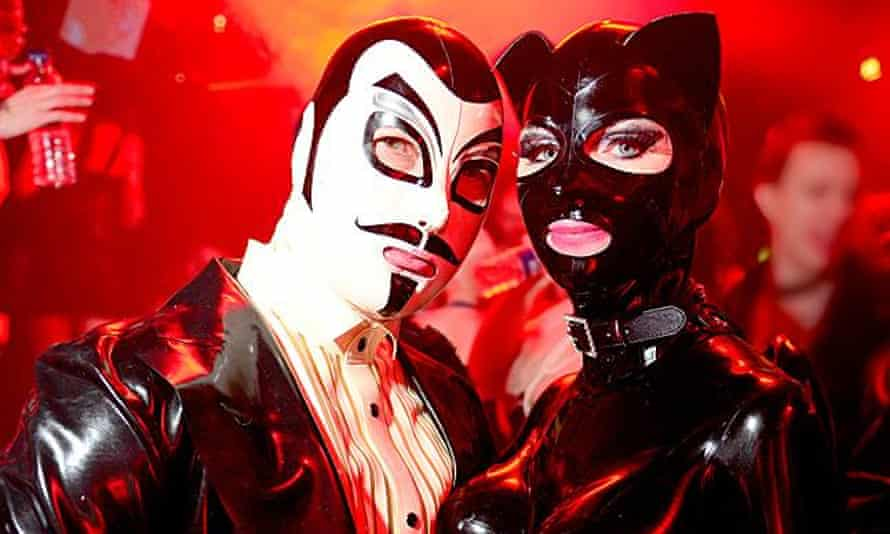 Guests, a man wearing white mask and a masked woman in a catsuit, at Torture Garden's club night. London.