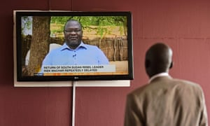 A man watches a news bulletin about Riek Machar's aborted return to Juba