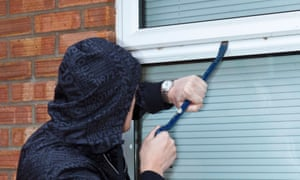 a man trying to force open a window on a house