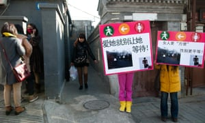 Protesters hold signs as part of the Occupying Toilets campaign