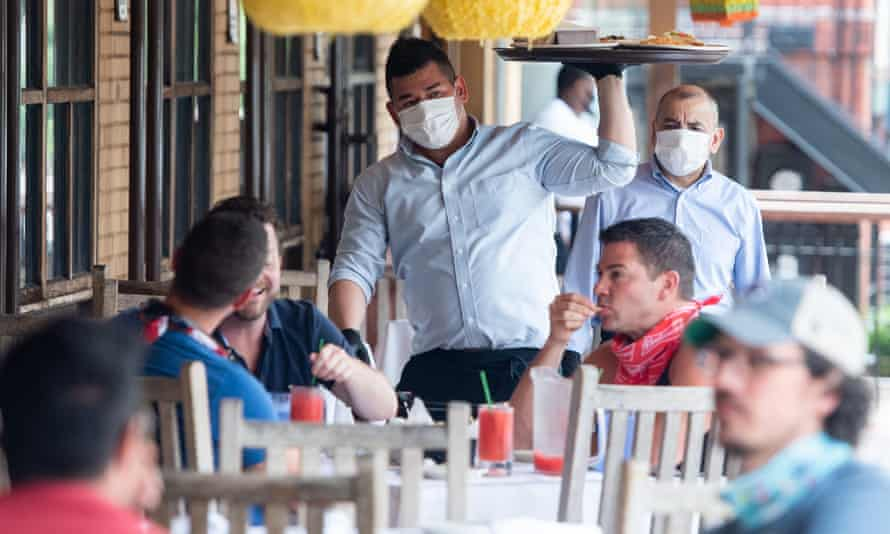 A waiter wearing masks and gloves delivers food to customers seated at an outdoor patio in Washington DC, on 29 May.