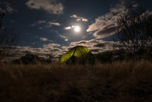 The full moon rises over a tent