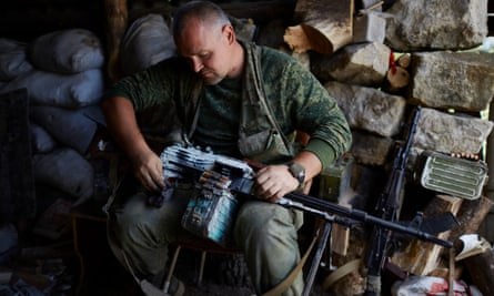 A militant cleans his gun on the northern frontline of Luhansk.