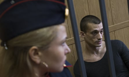 Petr Pavlensky sits in a cage in the courtroom in Moscow.
