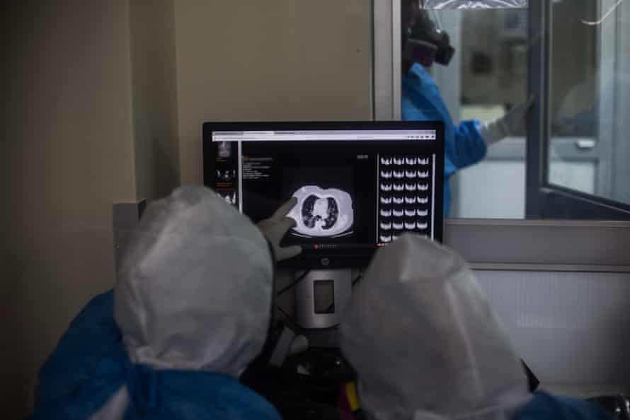 Medical personnel, assisting patients with COVID-19, look on a screen at Guillermo Almenara Hospital in Lima, Peru.