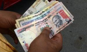 An Indian petrol pump employee counts rupee notes