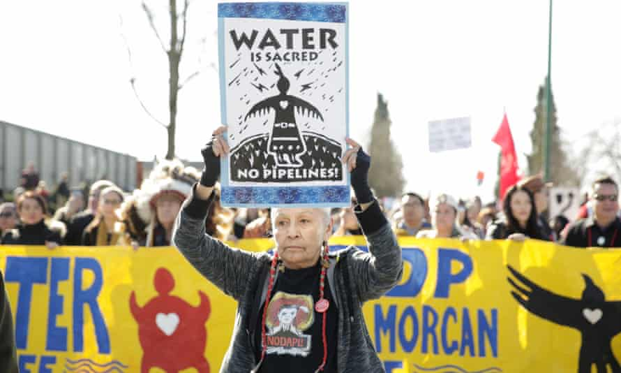 members of the Anishinaabe tribe march with others against the expansion of the Trans Mountain project in Burnaby, British Columbia on 10 March.