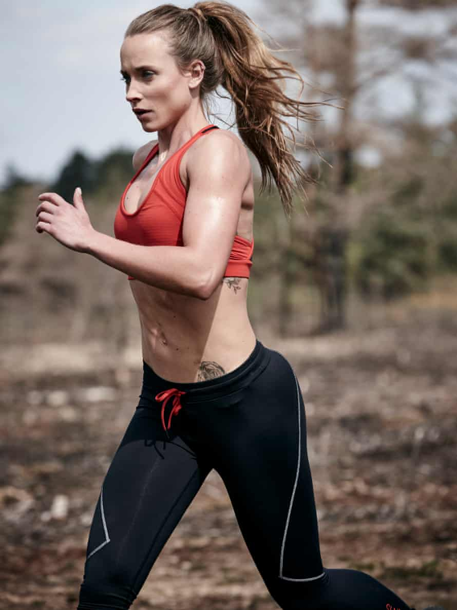 Woman with her long hair pulled back in a ponytail jogging in a sports bra and running tights
