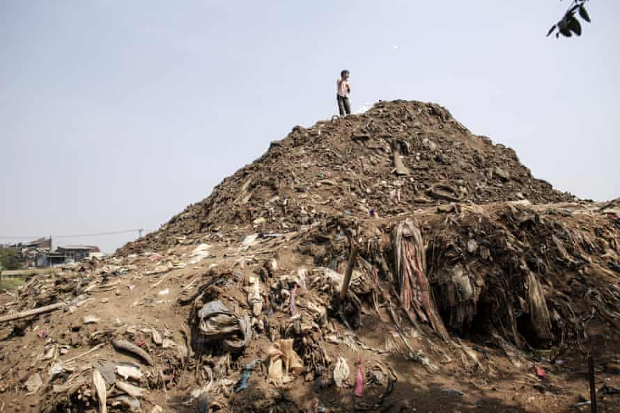 A child flies a kite on a mountain of sediment taken out of the Citarum in Dayeuhkolot.
