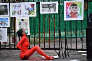 A protester covered in red paint demonstrates outside Bangkok remand prison
