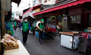 South Korean workers spray disinfectant at a market in Seoul.