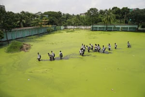 Bangladeshi school children walk through a flooded field as they return home after school at Demra in Dhaka. The mix of rain water and toxic waste from industries has turned the water green