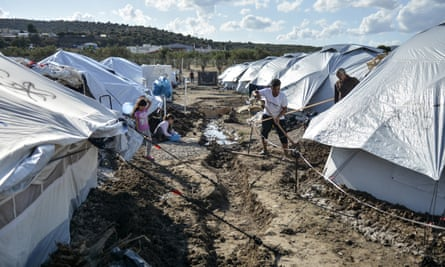 Refugees dig trenches to keep water out of their tents at the temporary Lesbos camp.