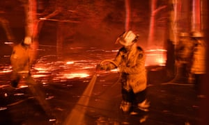 Firefighters hose down the area as they battle against bushfires around the town of Nowra on Tuesday