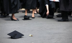 Students stand beside mortarboards thrown on the floor