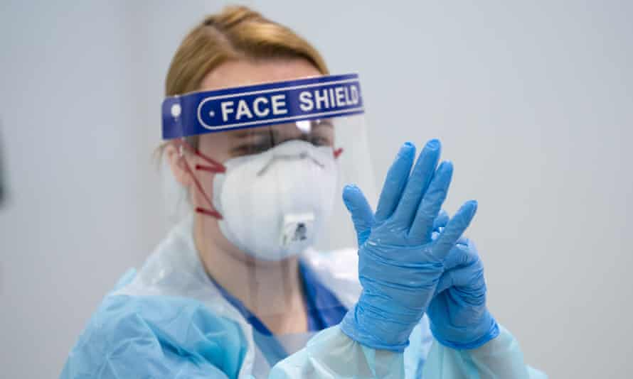 A staff member receives training on how to put on and remove PPE at the new Nightingale hospital in Manchester.