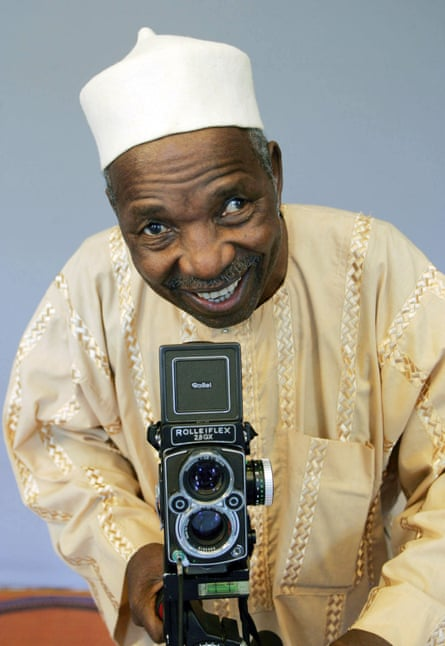 Malick Sidibé, smiling, with camera